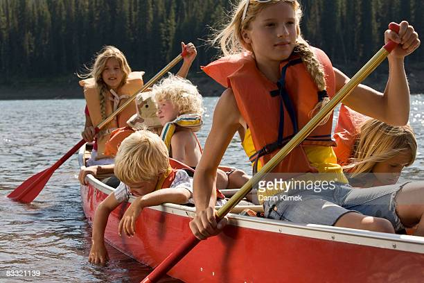 Kids canoeing in lake with mountain view