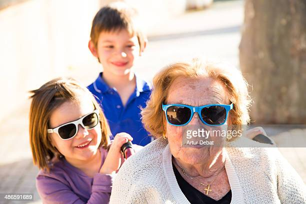 kids carry on his great-grandmother on wheelchair. - great granddaughter stock photos and pictures