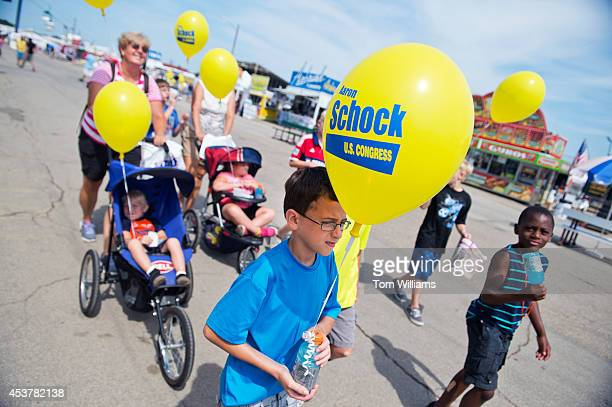 Kids carrying balloons supporting Aaron Schock RIll at the Illinois State Fair in Springfield Ill August 14 2014