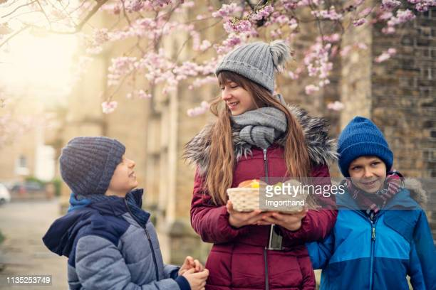 kids carrying easter basket to church - hot cross bun stock pictures, royalty-free photos & images