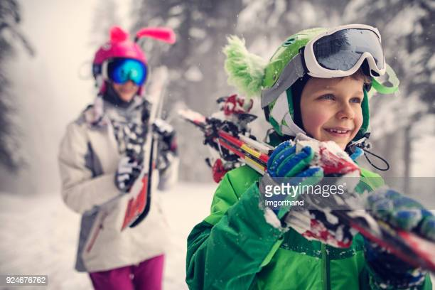 kids carrying skis on a beautiful winter day - ski stock pictures, royalty-free photos & images