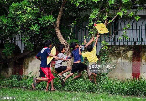 Kids chasing a kite in a Kolkata play ground.
