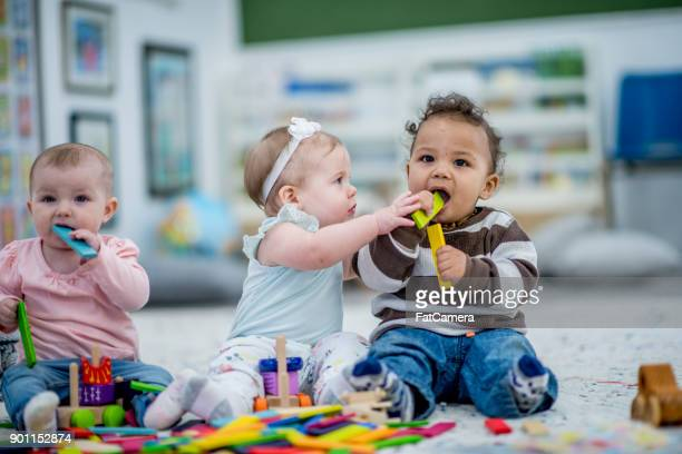 kids chewing on toys - child care stock pictures, royalty-free photos & images