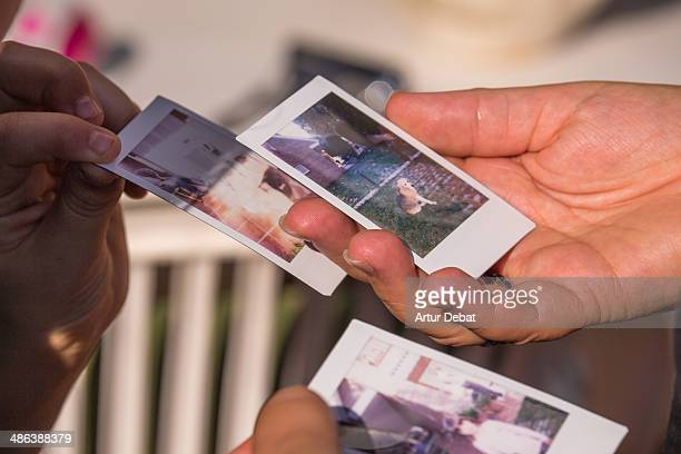Kids choosing revealed photos with Polaroid camera