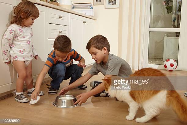 Kids cleaning up spilt milk off the floor