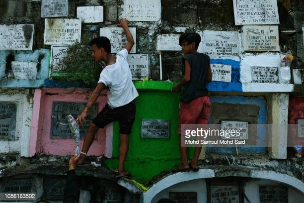Kids climb atop tombs to replace a candle of their relatives in a cemetery during the commemoration of All Saints' Day in Manila on November 1 2018...