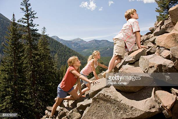 Kids climbing rocks with mountain view