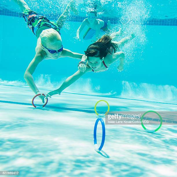 Kids (6-7) collecting diving rings underwater