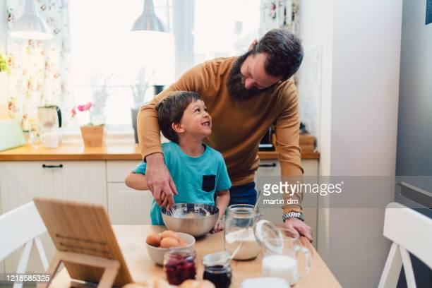 kids cooking at home during covid-19 pandemic - stay at home order stock pictures, royalty-free photos & images