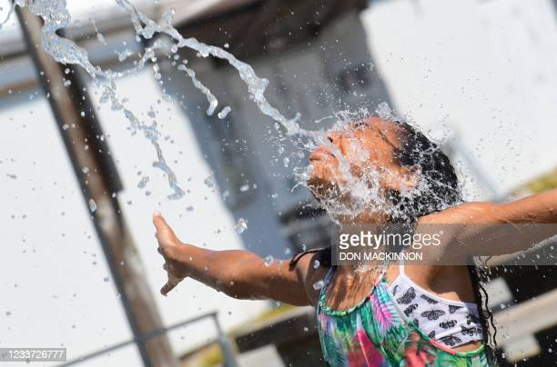 Kids cool off at a community water park on a scorching hot day in Richmond, British Columbia, June 29, 2021. - Schools and Covid-19 vaccination...