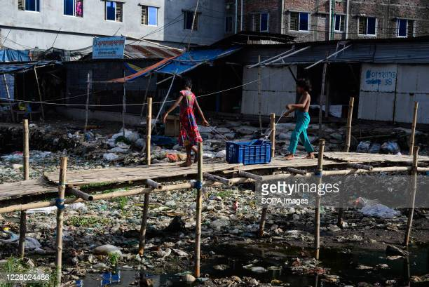 Kids crossing a river polluted with industrial garbage at bamboo bridge. Dhaka is going back to its normal life after some months of the ongoing...