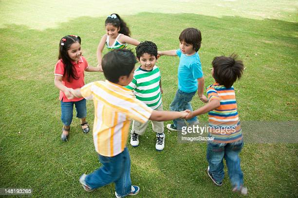 Kids (4-7) dancing in circle