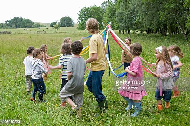 Kids dancing round maypole in meadow