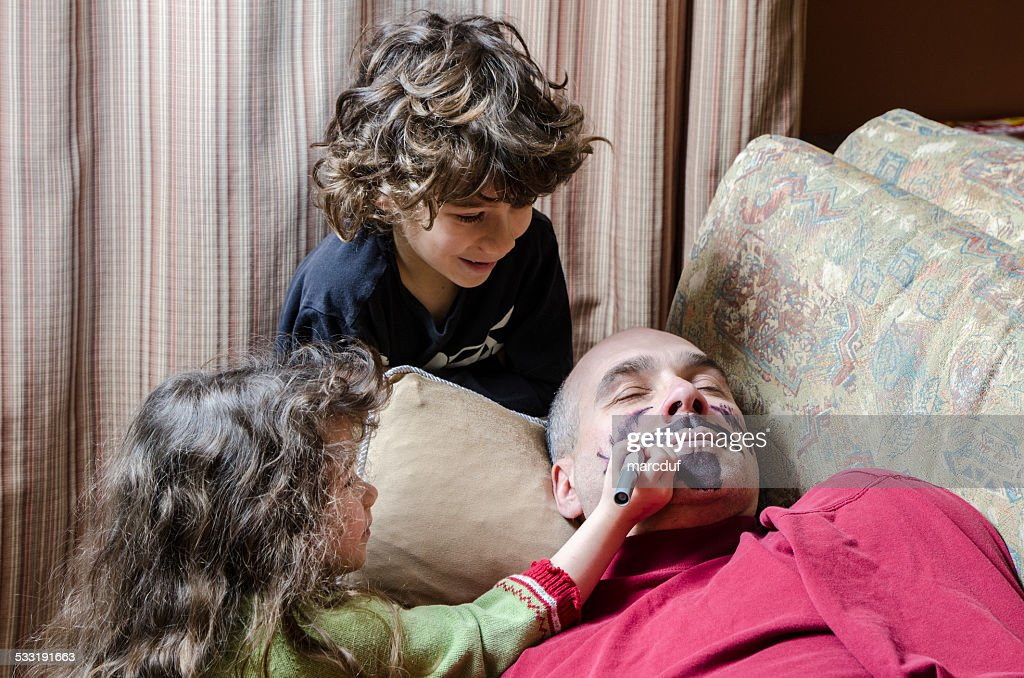 Kids drawing a mustache on father's face April fools day : Stock Photo