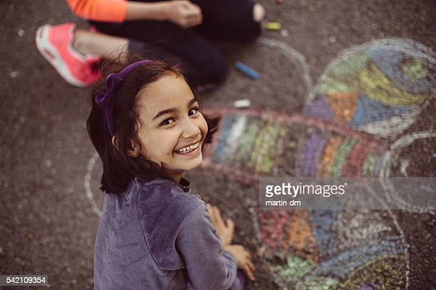 kids drawing with chalk on asphalt - chalk art equipment stock pictures, royalty-free photos & images