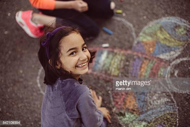 Los niños de dibujo con tiza en cemento