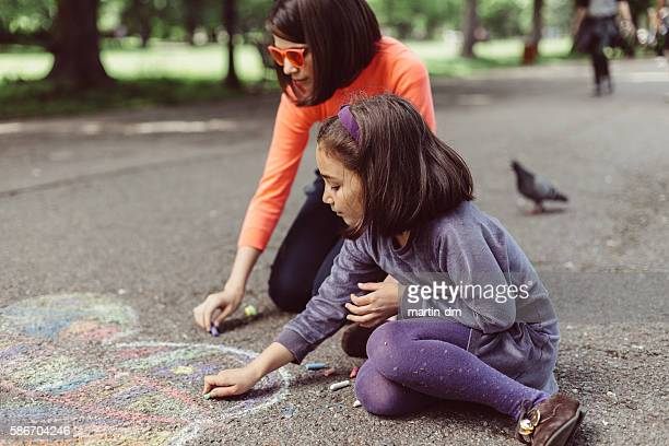 kids drawing with chalk on asphalt - chalk drawing stock pictures, royalty-free photos & images