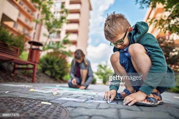 Kids drawing with chalk on sidewalk in residential area
