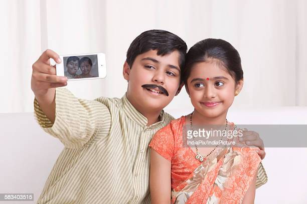 kids dressed as husband and wife taking a self portrait - mangala sutra fotografías e imágenes de stock