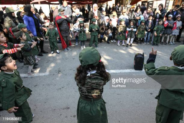 Kids dressed in military uniforms perform a theater piece on avenue Habib Bourguiba in the capital Tunis during the celebrations of the 9th...