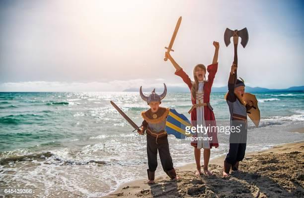 kinder, verkleidet als wikinger spielen am strand - wikinger stock-fotos und bilder
