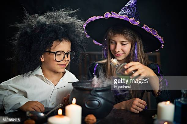 kids dressed up as witch and crazy scientist brewing potions - potion stock photos and pictures