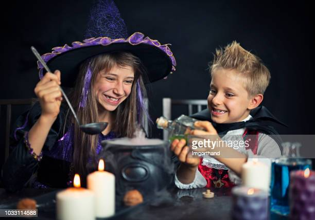 kids dressed up as witch and vampire brewing potions - potion stock photos and pictures
