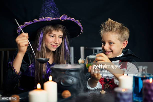 Kids dressed up as witch and vampire brewing potions