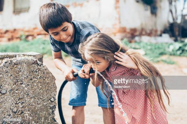 子供、ホースから水を飲む - 貧困 ストックフォトと画像