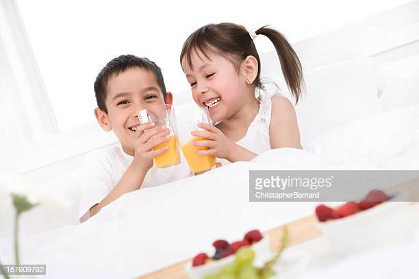 Niños comiendo un desayuno en la cama