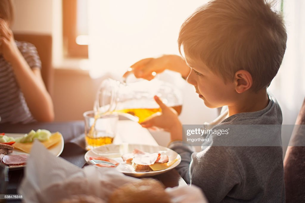 Kids eating breakfast on sunny morning