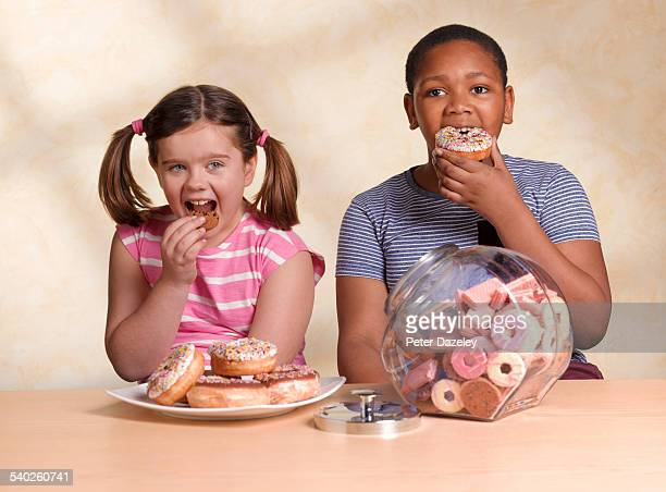 kids eating cookie and doughnut - fat people eating donuts stock pictures, royalty-free photos & images