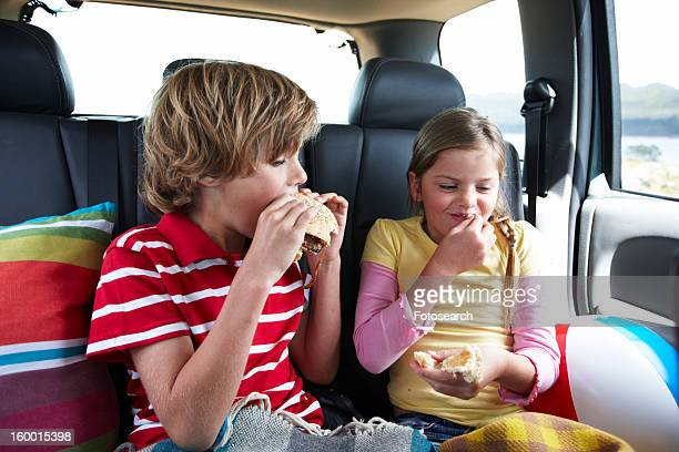 kids eating fast food - family inside car stock photos and pictures