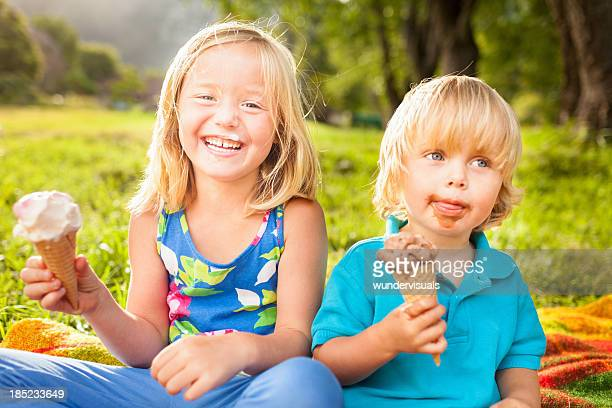 kids eating ice cream - girl sitting on boys face stock photos and pictures