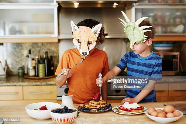 Kids eating pancakes in the kitchen with masks.