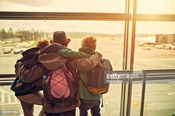 Kids embracing and looking at planes at the airport