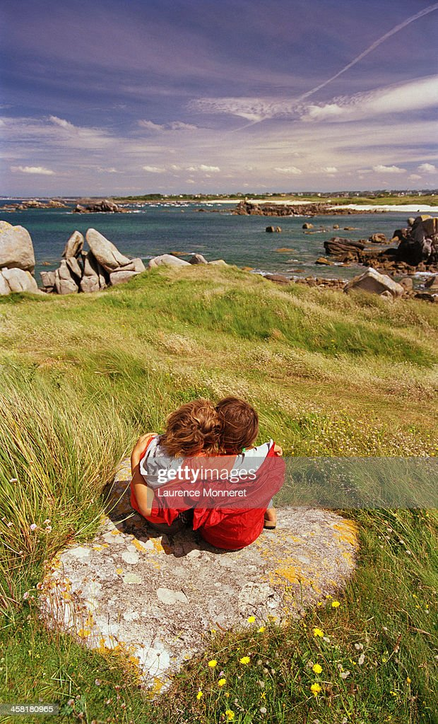 kids embracing sat on rock facing brittany seacost stock photo