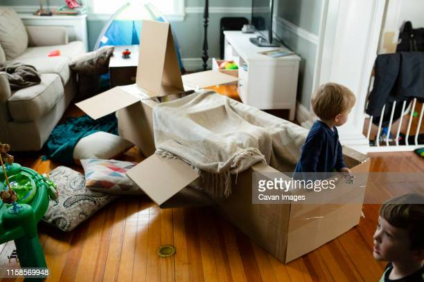 kids engage in pretend play indoors with spacecraft made of cardboard - fortress stock pictures, royalty-free photos & images