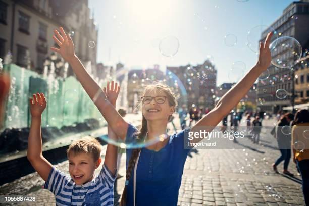 Kids enjoying bubbles in Market Square in Wrocław, Poland