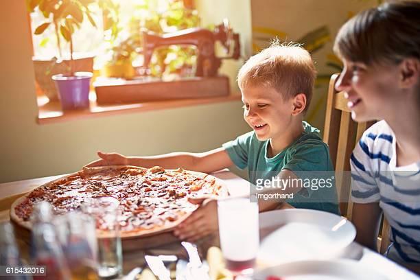 Kids enjoying giant pizza lunch