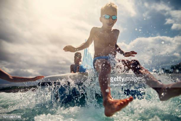 kids enjoying pedal boat and sliding to the sea - pedal boat stock pictures, royalty-free photos & images