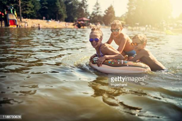 kids enjoying playing in lake - lake stock pictures, royalty-free photos & images