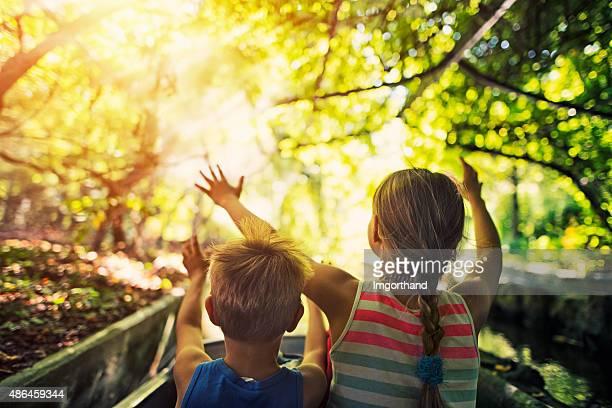 Kinder genießen Sie die Fahrt in einem Boot durch den Wald Fluss