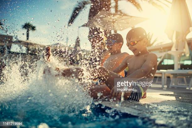 kids enjoying splashing in swimming pool - getting away from it all stock pictures, royalty-free photos & images