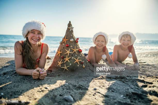 kids enjoying summer christmas - beach christmas stock pictures, royalty-free photos & images