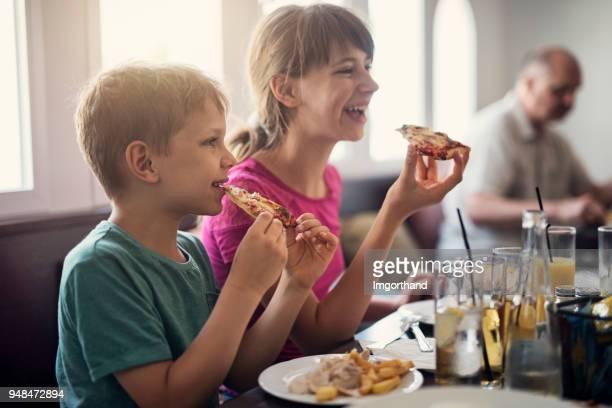 Kids enjoying tasty pizza in restaurant