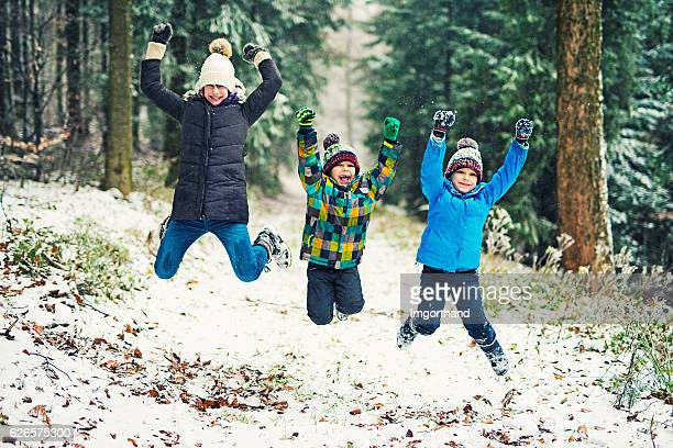 Kids enjoying the first snow in winter forest