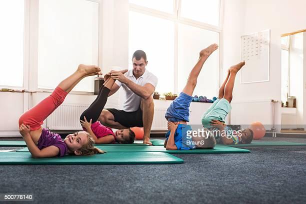 Enfants faisant de l'exercice dans un club de remise en forme avec leur entraîneur.