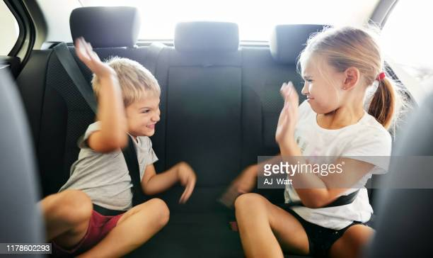 kids fighting in the car - fighting stock pictures, royalty-free photos & images