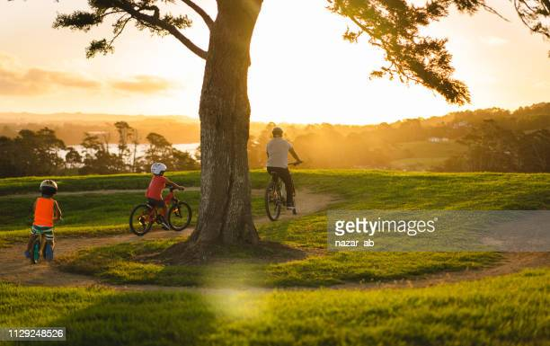 kids following father on bike. - auckland stock pictures, royalty-free photos & images